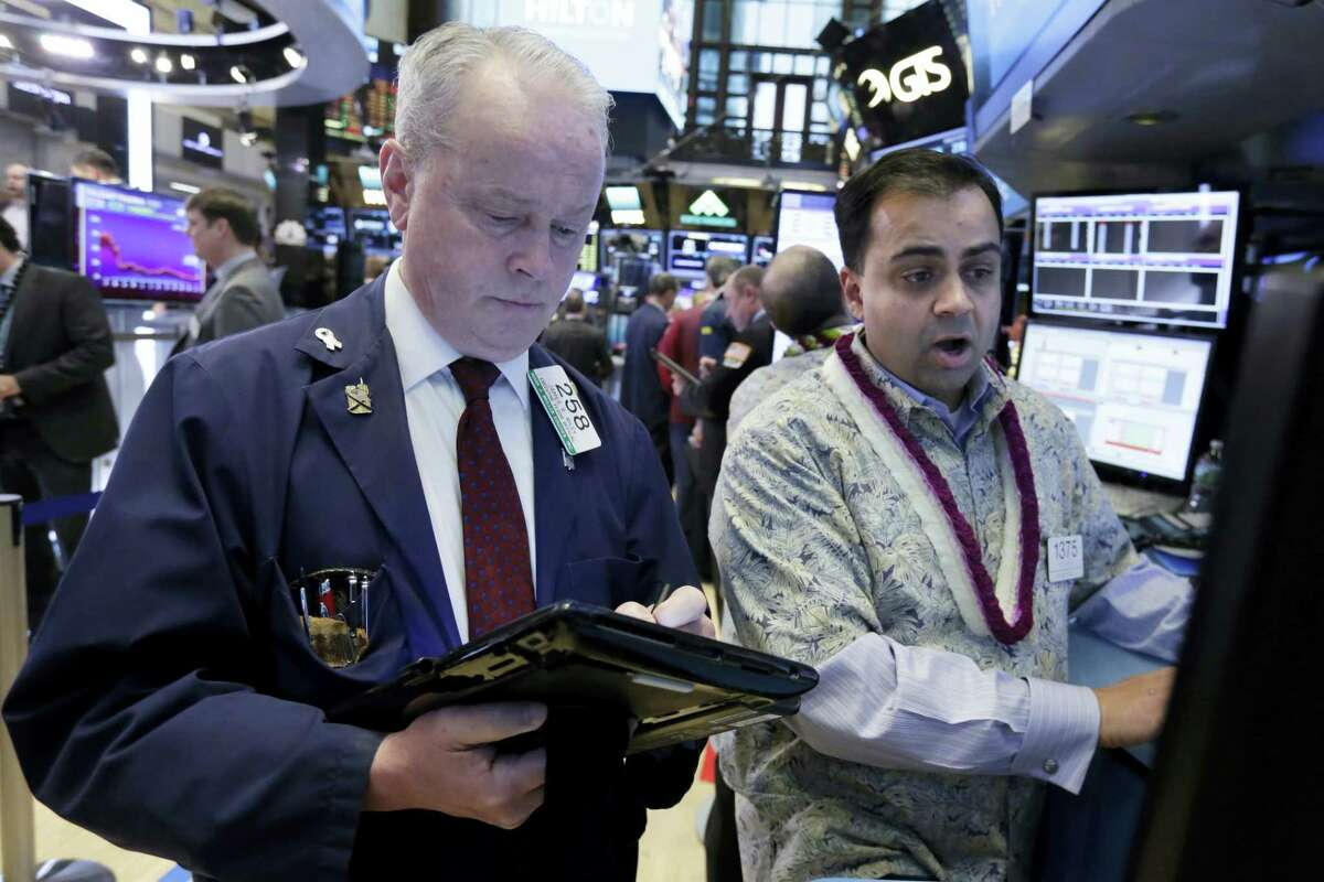 Trader James Riley, left, and specialist Dilip Patel work on the floor of the New York Stock Exchange Tuesday.
