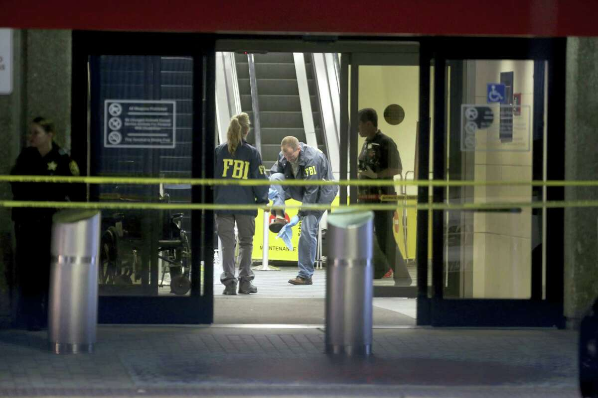 An FBI agent wipes off his shoe while working the crime scene in Terminal 2 at Ft. Lauderdale-Hollywood International Airport, Saturday, Jan. 7, 2017, the day after a shooting in the baggage area.
