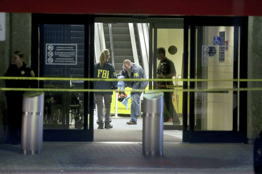 An FBI agent wipes off his shoe while working the crime scene in Terminal 2 at Ft. Lauderdale-Hollywood International Airport, Saturday, Jan. 7, 2017,  the day after a shooting in the baggage area. Photo: Mike Stocker — South Florida Sun-Sentinel Via AP / Sun Sentinel 2016