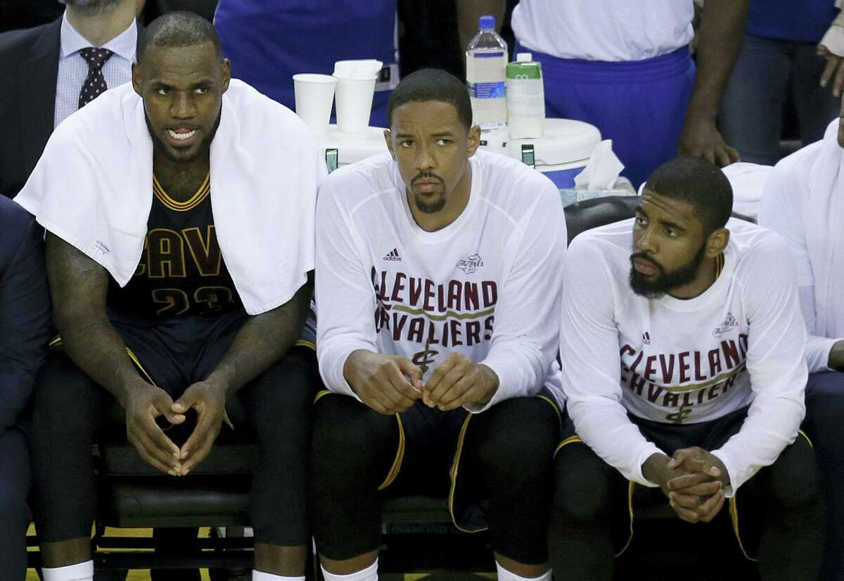 Cleveland Cavaliers forward LeBron James, from left, sits on the bench with center Tristan Thompson and guard Kyrie Irving during the second half of Game 1 of the NBA Finals against the Golden State Warriors in Oakland Thursday.