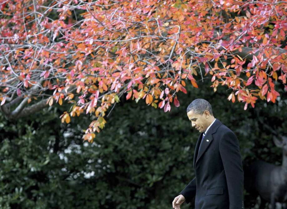 In this Dec. 6, 2010 photo, President Barack Obama walks across the South Lawn of the White House in Washington, to board Marine One helicopter as he travels to Winston-Salem, N.C. More than half of Americans view President Barack Obama favorably as he leaves office, a new poll shows, but Americans remain deeply divided over his legacy. Less than half of Americans say they're better off eight years after his election or that Obama brought the country together. Photo: AP Photo/Charles Dharapak, File   / AP2010