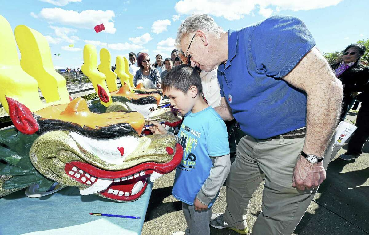 Anderson De Graaf (center), 7, of Hamden and Andrew Wolf (right), director of the New Haven Department of Arts, Culture and Tourism, participate in the Eye-Dotting Ceremony to awaken the dragons before the start of the Canal Dock/New Haven Dragon Boat Regatta by the Long Wharf Pier in New Haven on Saturday.