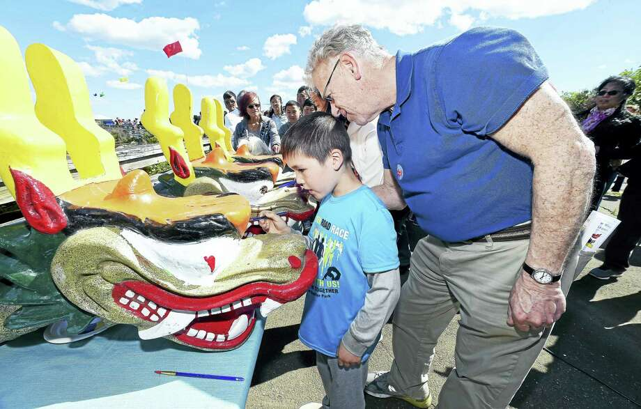 Anderson De Graaf (center), 7, of Hamden and Andrew Wolf (right), director of the New Haven Department of Arts, Culture and Tourism, participate in the Eye-Dotting Ceremony to awaken the dragons before the start of the Canal Dock/New Haven Dragon Boat Regatta by the Long Wharf Pier in New Haven on Saturday. Photo: Arnold Gold — New Haven Register