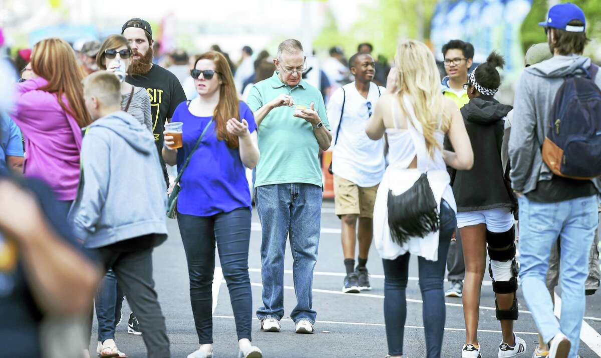 Arnold Gold — New Haven Register Pedestrians walk along Long Wharf Drive in New Haven during the third annual Food Truck Festival on Saturday.