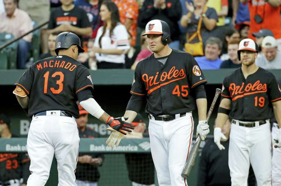 Baltimore Orioles' Mark Trumbo (45) greets teammate Manny Machado after Machado hit a solo home run in the first inning of a baseball game against the Boston Red Sox in Baltimore, Friday, June 2, 2017. (AP Photo/Patrick Semansky) Photo: AP / Copyright 2017 The Associated Press. All rights reserved.