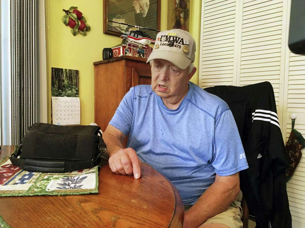 Retired coal miner Kenny Smith sits at his kitchen table in Centertown, Ky., Thursday, June 1, 2017, as he speaks during an interview. President Donald Trump announce Thursday during a news conference a decision to pull out of the landmark Paris climate accord. Smith worked in underground mines in western Kentucky until he retired in the 1990s after 22 years. He supports Trumps decision to pull out of the accord. Next to Smith on the table is the heart pump that keeps him alive.