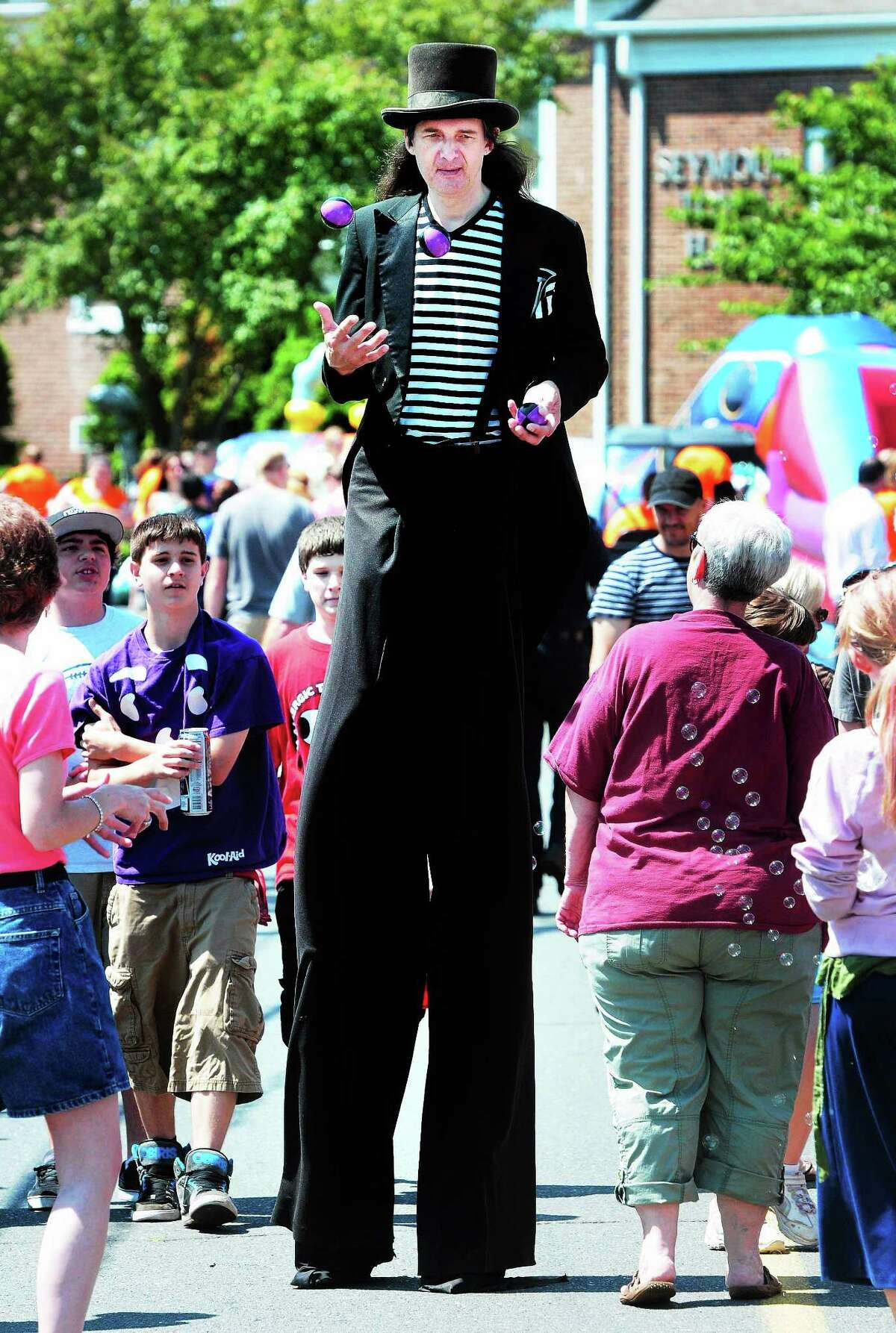 """Arnold Gold — New Haven Register FILE PHOTO Andy """"The Amazing Andy"""" Charney juggles while walking on stilts on First Street during the Seymour Founders' Day 2012 celebration."""