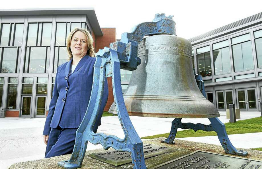 Clinton Superintendent of Schools Maryanne O'Donnell is photographed by the original bell from Morgan School near the back entrance to the new Morgan School in Clinton. Photo: Arnold Gold — New Haven Register