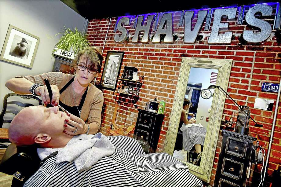 "Barber Susan Hushin, owner of BBS Shave Studio at 58 River St. in Milford, uses a straight razor to give Milford resident Bill Parry a wet shave known as a ""Mr. Slick with a Gentleman's Shave. Photo: Catherine Avalone — New Haven Register   / New Haven RegisterThe Middletown Press"