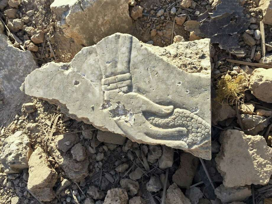 A fragment of an Assyrian-era relief shows the image of a genie holding a pine cone at the ancient site of Nimrud that was destroyed by Islamic State group militants near Mosul, Iraq. in this Nov. 28, 2016, photo. In the 9th and 8th centuries BC, Nimrud was the capital of the Assyrian Empire, which burst out of Northern Mesopotamia to conquer much of the Mideast. The remains of its palaces, reliefs and temples were methodically blown up and torn to pieces by the Islamic State group in early 2015 in its campaign to erase history. Photo: AP Photo/Maya Alleruzzo    / Copyright 2016 The Associated Press. All rights reserved.