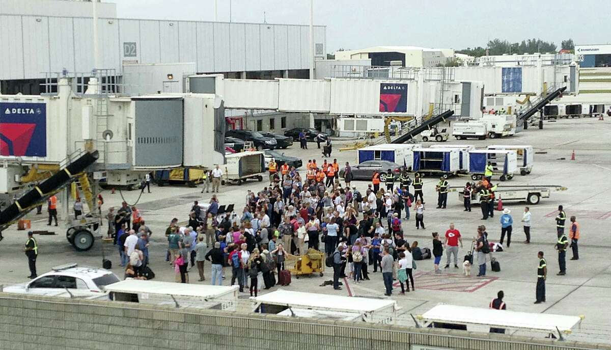 People stand on the tarmac at the Fort Lauderdale-Hollywood International Airport after a shooter opened fire inside a terminal of the airport, killing at least five people and wounding others before being taken into custody, Friday, Jan. 6, 2017, in Fort Lauderdale, Fla.