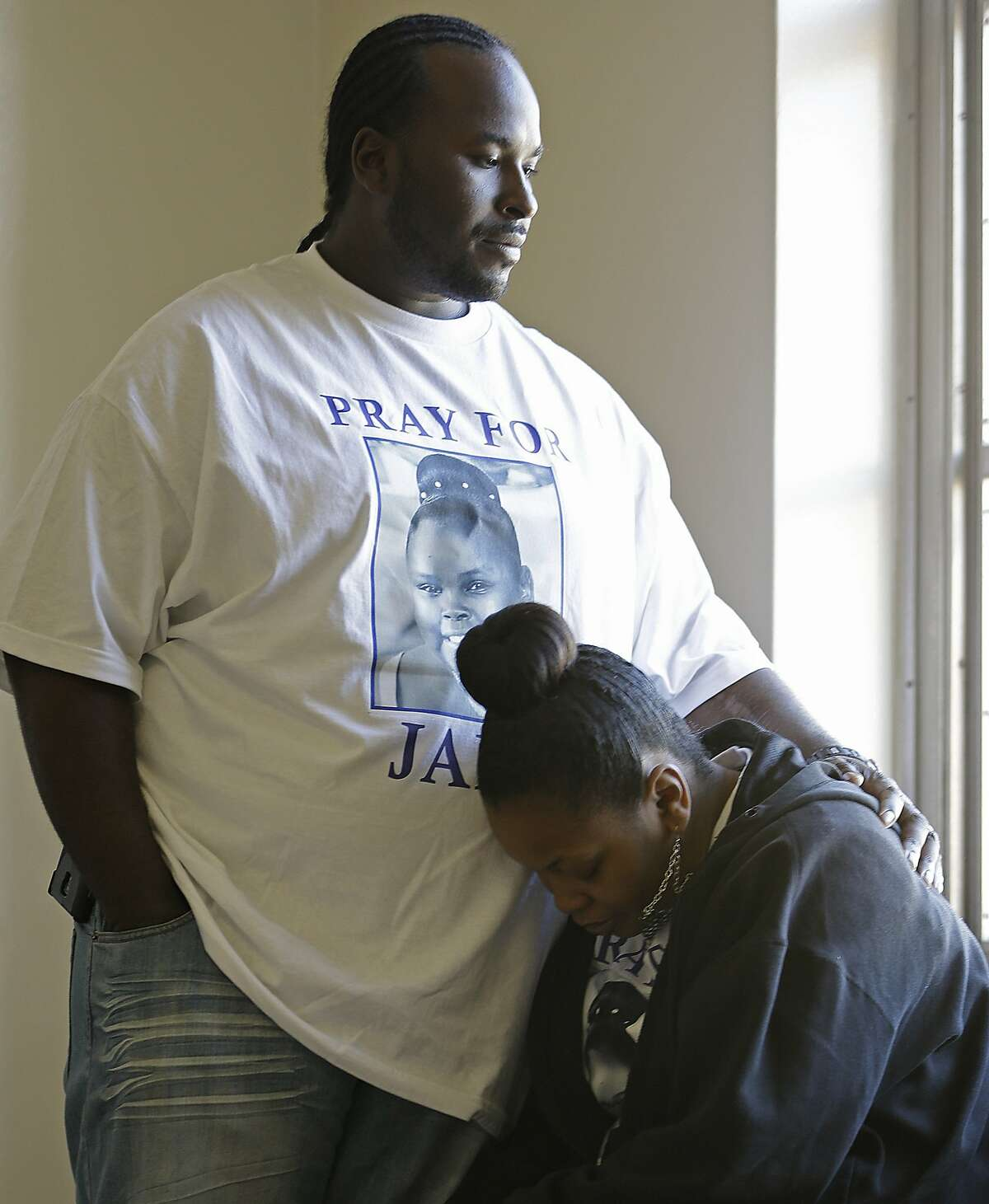 FILE - Marvin Winkfield places his arm around his wife Nailah Winkfield, mother of 13-year-old Jahi McMath, as they wait outside a courtroom in Oakland in this Friday, Jan. 3, 2014 file photo.