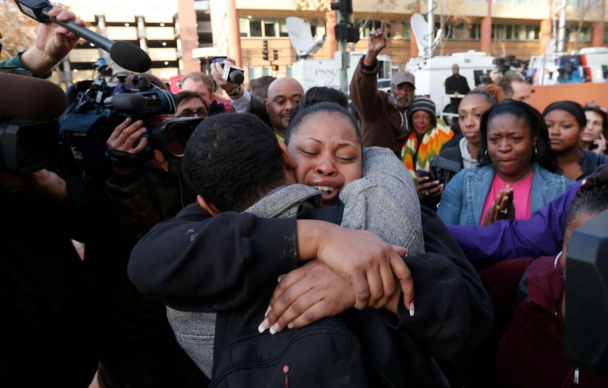 FILE - The mother of Jahi McMath, Nailah Winkfield embraces her brother Omari Sealey, after they stated that the court order to remove Jahi from a ventilator has been extended in this Dec. 30, 2013 file photo. The statement was made by the family to the news media in front of Children's Hospital in Oakland.