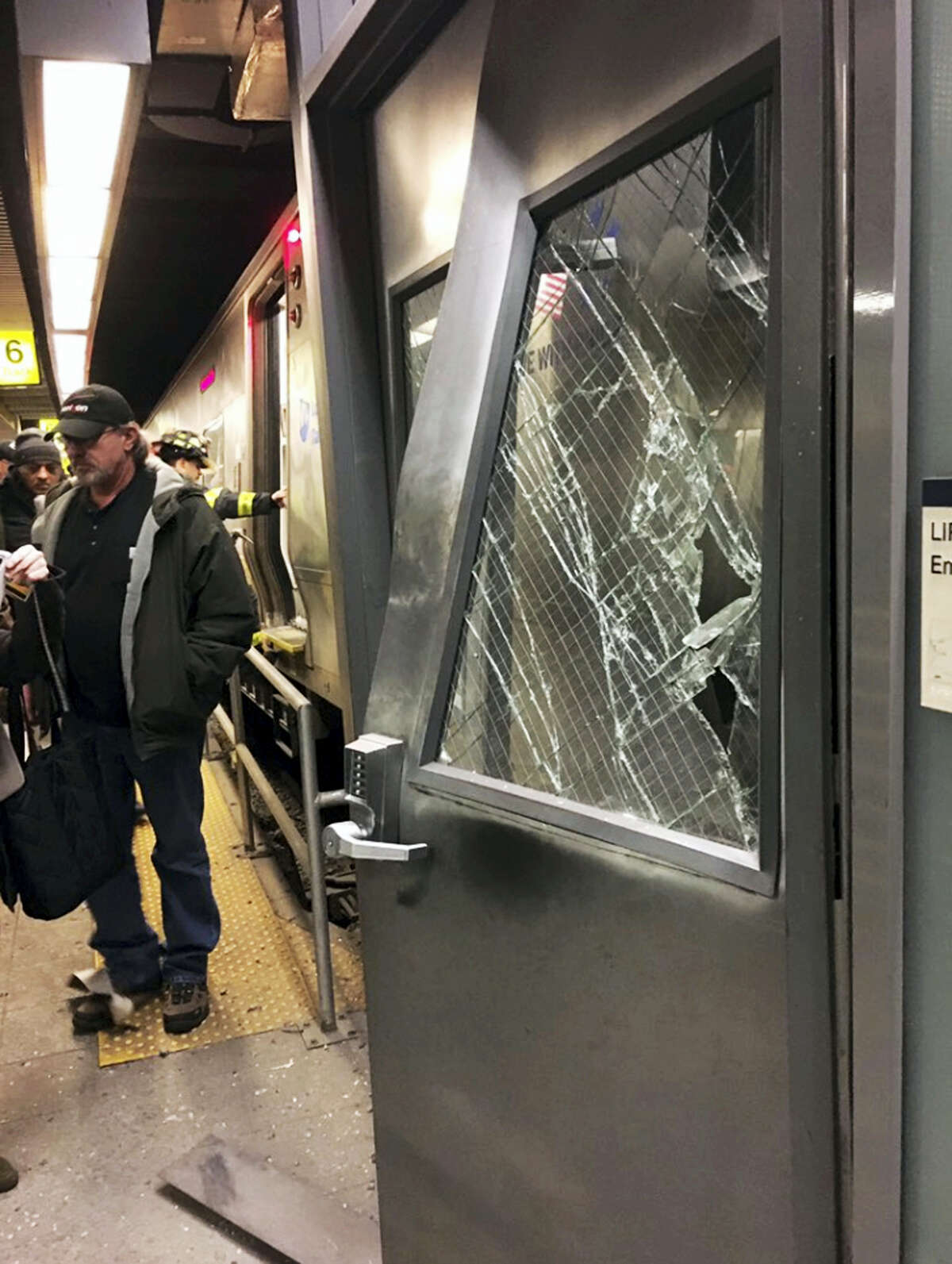 Emergency personnel work at the scene at Atlantic Terminal after New York City authorities said a Long Island Rail Road train either hit a bumping block or derailed at the station in the Brooklyn borough of New York, Wednesday, Jan. 4, 2017.