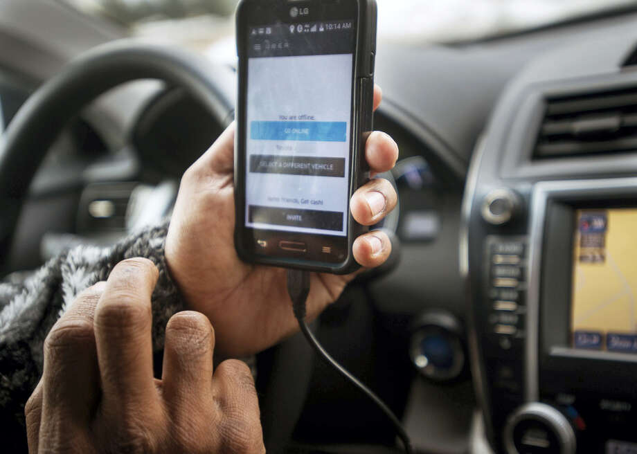 Mohammad Uddin checks his smartphone he uses to provide rides via the Uber app. Photo: Paul Kuehnel - Daily Record/Sunday News   / YORK DAILY RECORD/SUNDAY NEWS