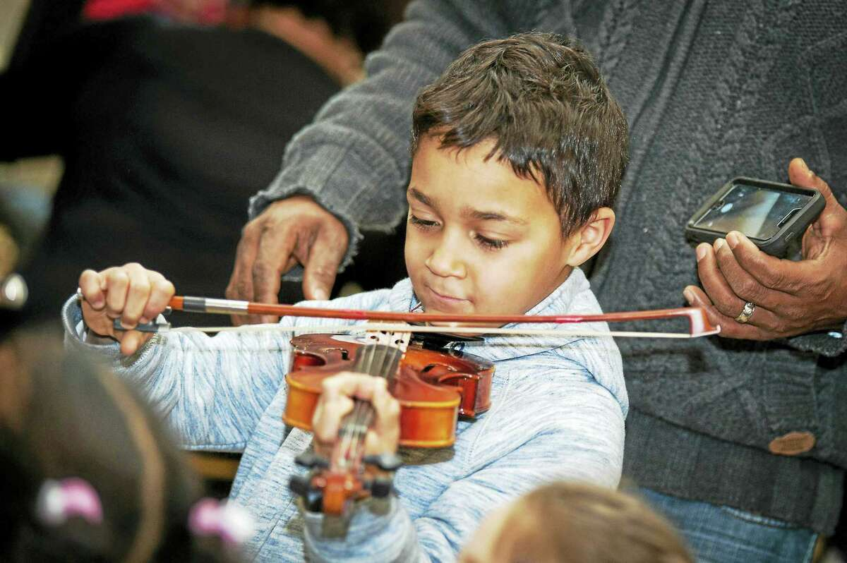 A local child tries out a violin at the Instrument Discovery Zone.