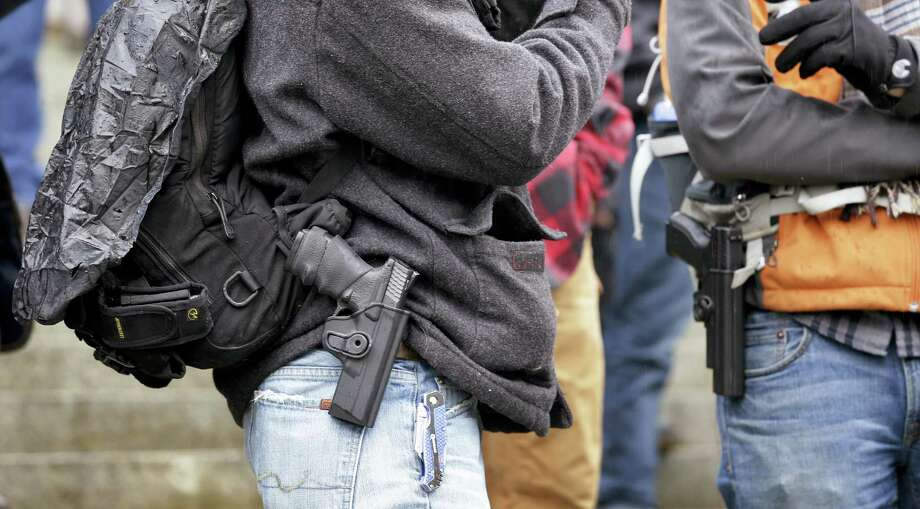Men stand with pistols strapped at their sides at a gun rights rally on the steps of the Capitol Friday, Jan. 15, 2016, in Olympia, Wash. Lawmakers and others spoke at the rally, which drew about 100 people, emphasizing legislative priorities and speaking against gun-related policies of President Barack Obama, like his recent executive actions to expand background checks to cover more firearms sold at gun shows, and elsewhere. Photo: AP / AP