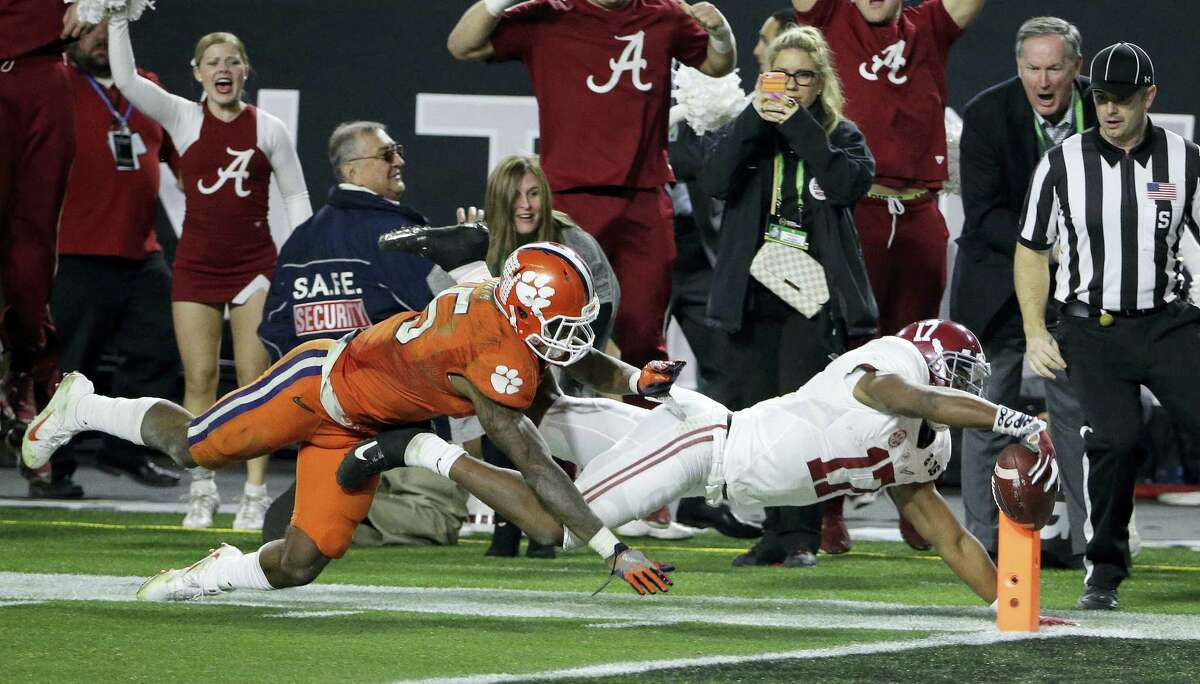 In a Jan. 11, 2016 photo, Alabama's Kenyan Drake gets past Clemson's T.J. Green as he runs back a kick off for a touchdown during the second half of the NCAA college football playoff championship game in Glendale, Ariz. A year ago, Alabama beat Clemson 45-40 in a thriller. This is the first time in the college football title-game era that same two teams got to the season's final matchup. Alabama and Clemson play in Tampa, Fla. on Monday night.