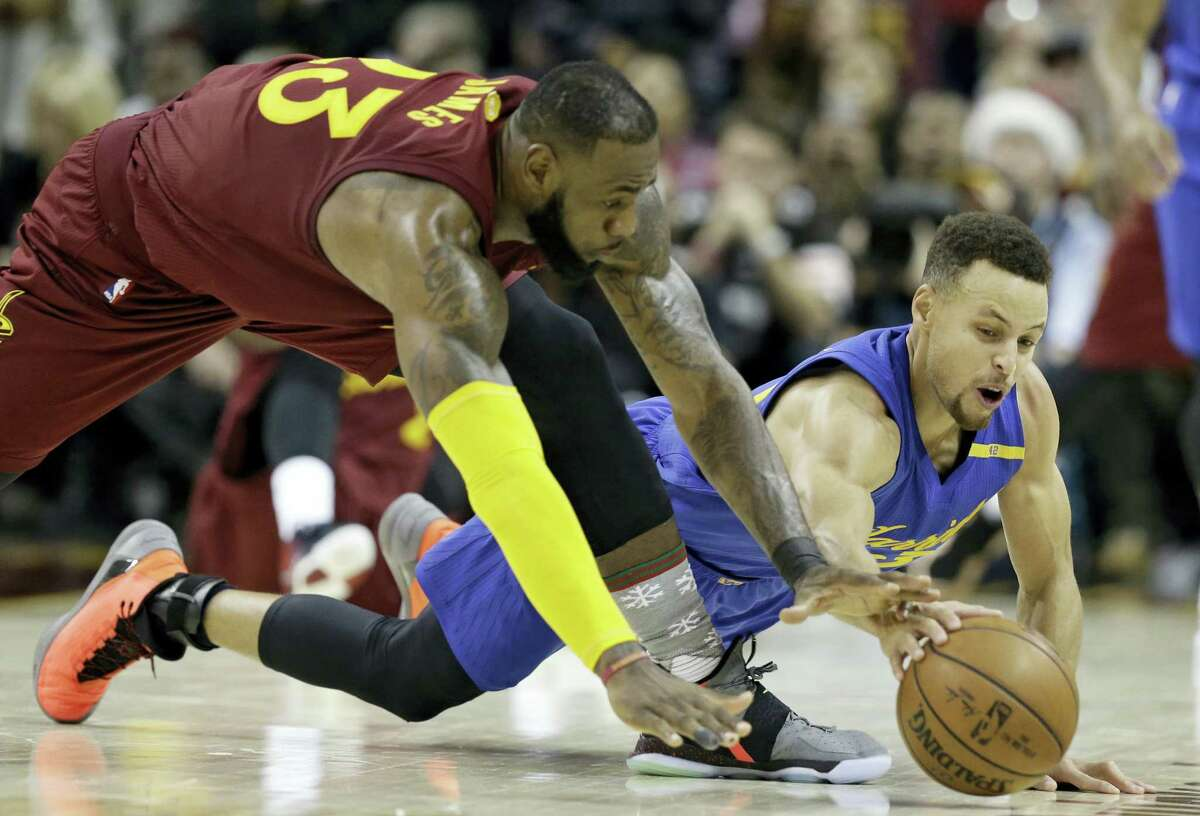 Cleveland Cavaliers' LeBron James, left, and Golden State Warriors' Stephen Curry battle for a loose ball in the second half of an NBA basketball game Dec. 25, 2016 in Cleveland. The Cavaliers won 109-108.