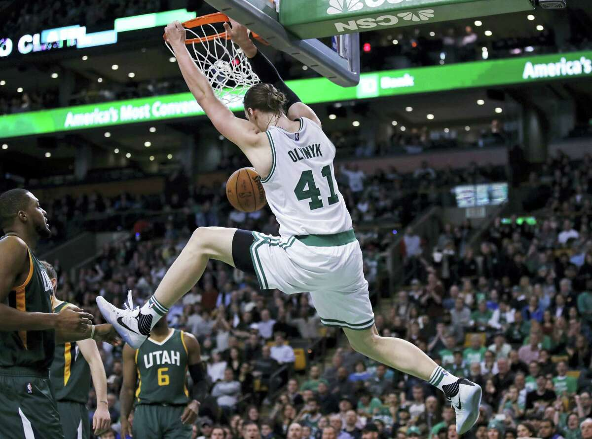 Boston Celtics center Kelly Olynyk hangs on the rim on a dunk during the second half against the Utah Jazz in Boston, Tuesday. The Celtics defeated the Jazz 115-104.