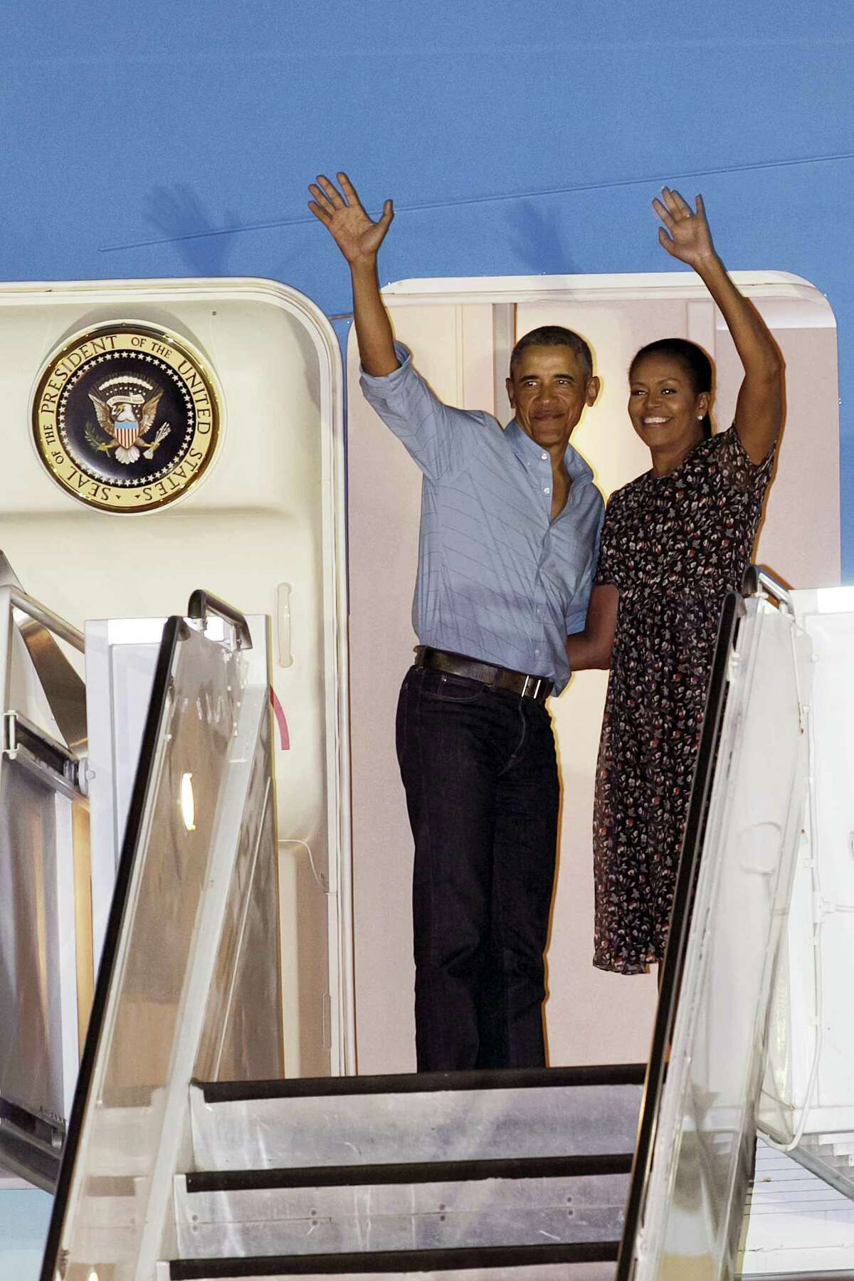 U.S. President Barack Obama and first lady Michelle Obama wave at people from Air Force One as they leave Joint Base Pearl Harbor-Hickam, adjacent to Honolulu, Hawaii, en route to Washington on Jan. 1, 2017 after their annual family vacation on the island of Oahu.