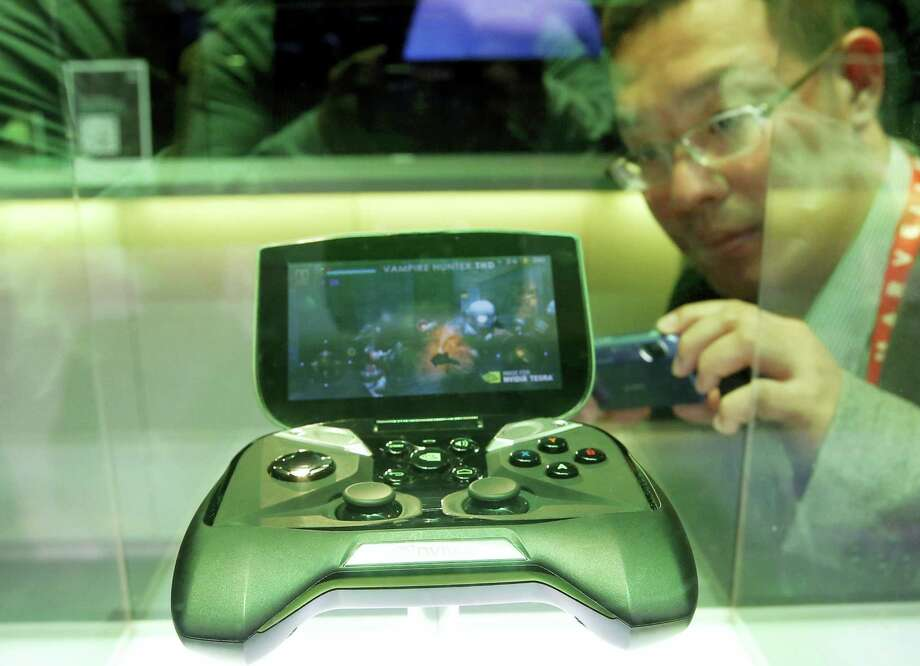 Nvidia's portable handheld gaming device, the Project Shield, is on display at the company's booth at the International Consumer Electronics Show in Las Vegas in 2013. Chipmaker Nvidia more than tripled in value in 2016, far more than any other company on the S&P 500. Photo: Jae C. Hong — AP File Photo / AP2013