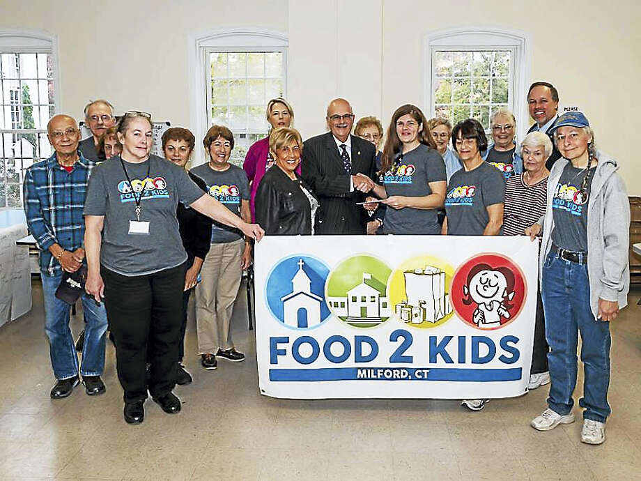 United Way of Milford is one of many community organizations rallying around the Food 2 Kids ministry. Here, United Way Executive Director Gary Johnson, center, makes a donation to the program. Photo: Contributed Photo   / UCC Milford