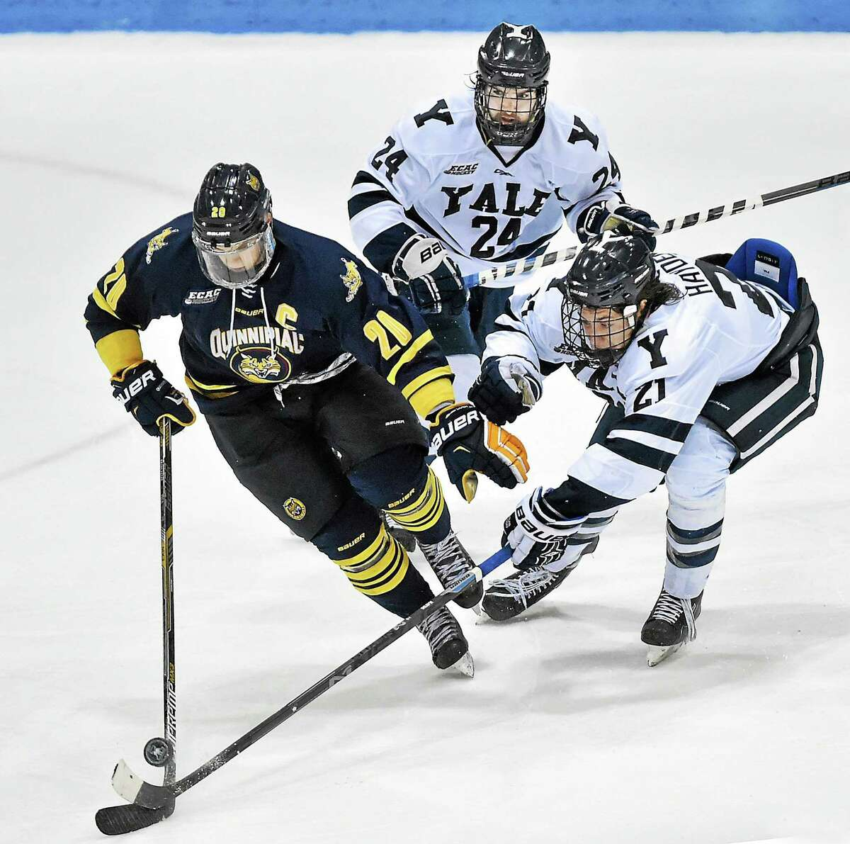 Quinnipiac's Matthew Peca (20) and Yale's John Hayden (21) and Mike Doherty (24) battle for posession. The Yale Bulldogs and the Quinnipiac Bobcats tied 2-2 in regulation play at Ingalis Rink at Yale University in New Haven, Saturday, January 31, 2015. After one 5-minute OT, the score remained, 2-2. (Catherine Avalone/New Haven Register)