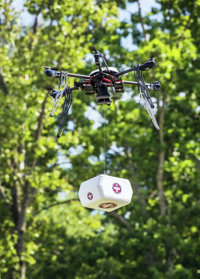 Tim C Cox/The Bristol Herald-Courier via AP   A Flirtey drone flies above the Wise County Fairgrounds in 2015 while lowering a package of prescription medication at the Remote Area Medical clinic in Wise County, Va. Photo: AP / The Bristol Herald-Courier