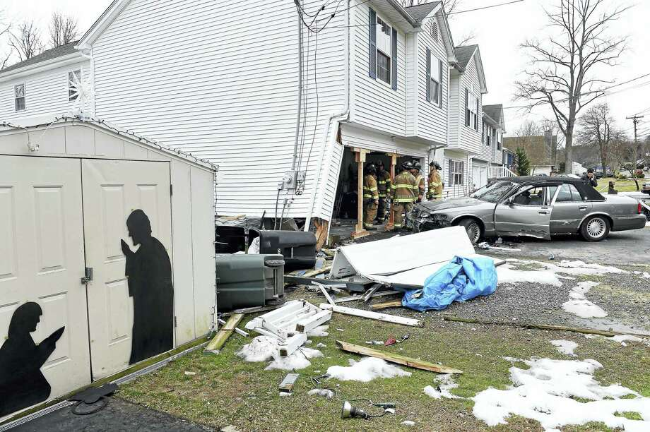 Members of the Milford Fire Department finish bracing a house at 1019 New Haven Ave. in Milford where a car collided on 12/26/2016. Photo: Arnold Gold-New Haven Register