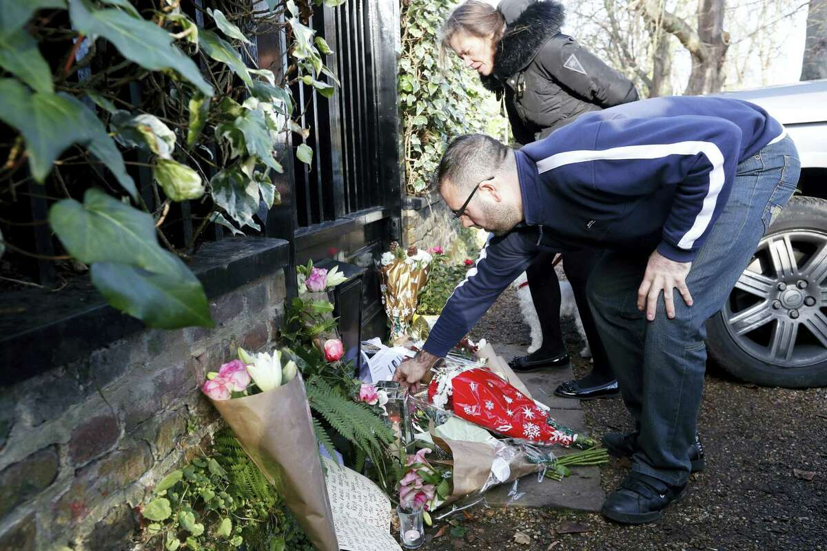 Fans leave tributes outside the home of British musician George Michael in London, Monday. George Michael, who rocketed to stardom with WHAM! and went on to enjoy a long and celebrated solo career lined with controversies, has died, his publicist said Sunday. He was 53.