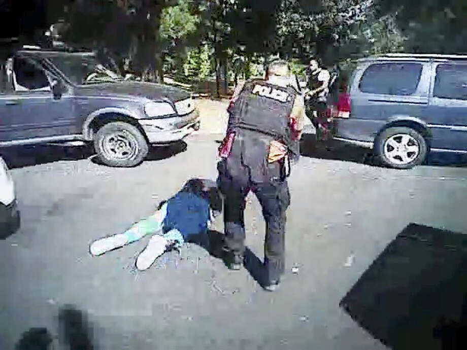 This image made from video provided by the Charlotte-Mecklenburg Police Department on Saturday shows Keith Scott on the ground as police approach him in Charlotte, N.C., on.   Charlotte-Mecklenburg District Attorney Andrew Murray announced Wednesday that the shooting by officer Brent Vinson was justified.  Vinson, who is black, shot and killed Keith Lamont Scott on Sept. 20. Photo: Charlotte-Mecklenburg Police Department Via AP   / Charlotte-Mecklenburg Police Department