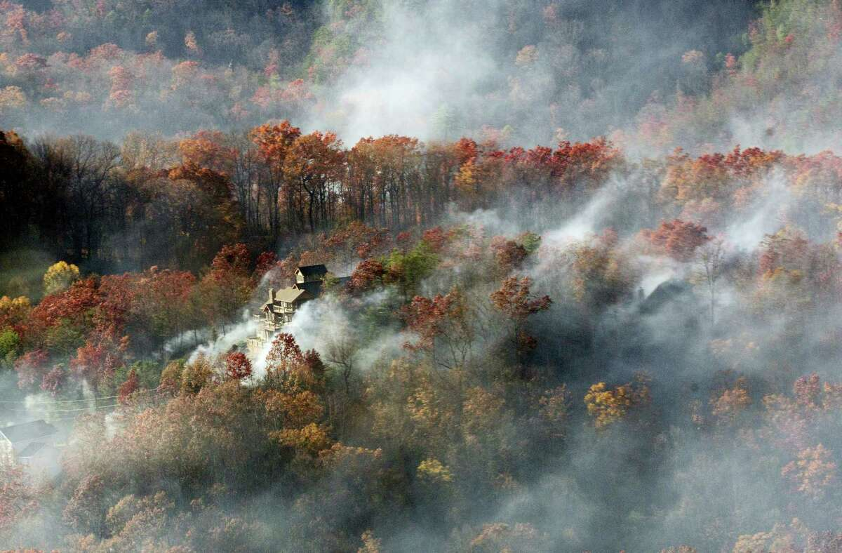 Smoke surrounds a home as seen from aboard a National Guard helicopter near Gatlinburg, Tenn., Tuesday, Nov. 29, 2016. Thousands of people have fled deadly wildfires that have destroyed hundreds of homes and a resort in the Great Smoky Mountains.