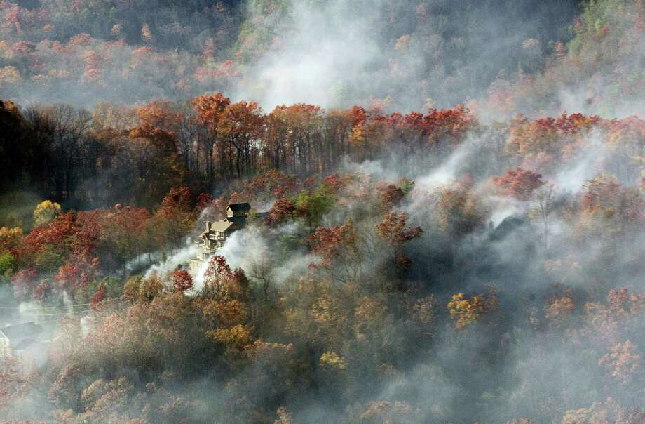 Smoke surrounds a home as seen from aboard a National Guard helicopter near Gatlinburg, Tenn., Tuesday, Nov. 29, 2016. Thousands of people have fled deadly wildfires that have destroyed hundreds of homes and a resort in the Great Smoky Mountains. Photo: Erik Schelzig — AP Photo   / Copyright 2016 The Associated Press. All rights reserved.