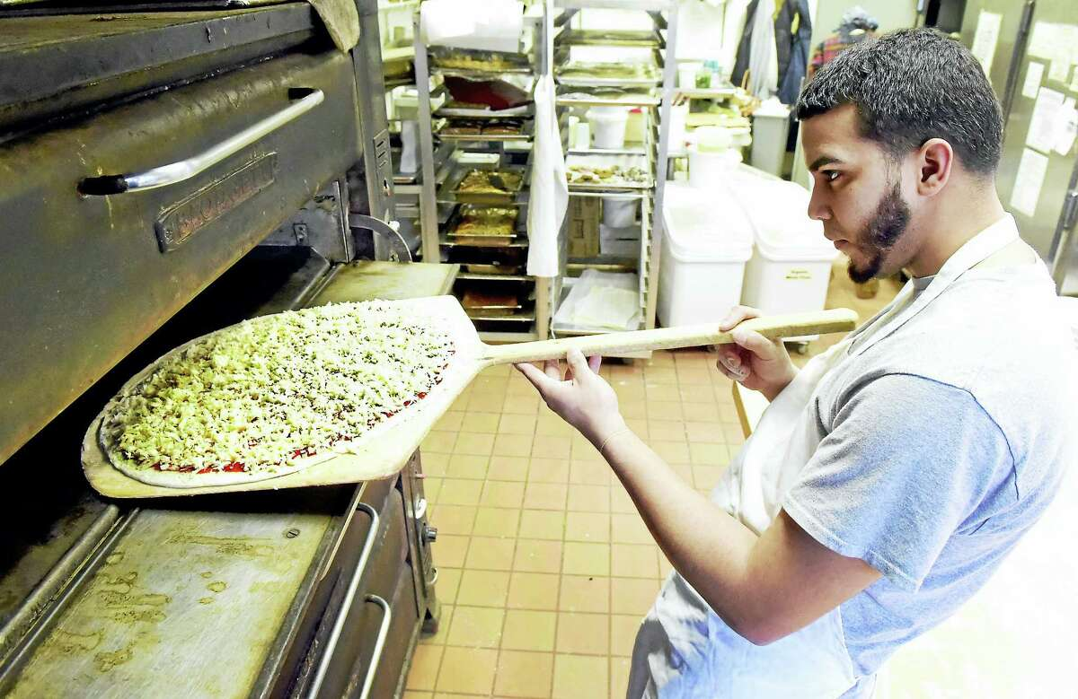 Pizza maker Kevin Feliciano, an employee at the Edge of the Woods in New Haven, makes a kosher pizza.