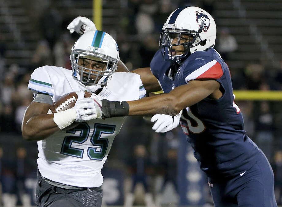 UConn's Obi Melifonwu tackles Tulane running back Josh Rounds. Photo: The Associated Press File Photo   / FR158029 AP