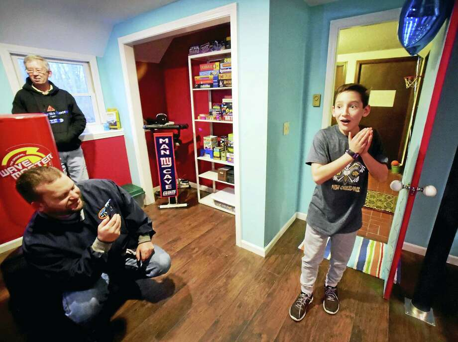"""Isaac Adler, 13, of Clinton is surprised when his renovated basement play space, the """"Man Cave"""" ,was revealed in a surprise showing at his home Thursday, December 22, 2016. The play space was made possible by the Make-A-Wish Foundation. Isaac has Hemophilia A and Chron's Disease. At rear, left in photo is professional painter Rob Lunn of Chester and carpenter Jeff Wolcheski of Local 24 Carpenters Union in Wallingford, both of whom donated their time renovating the basement room into Adler's  play space. Photo: Peter Hvizdak — New Haven Register   / ©2016 Peter Hvizdak"""
