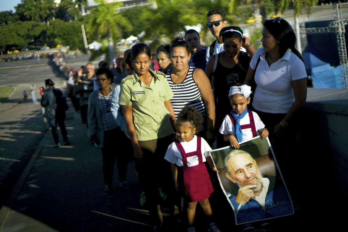 A child holds a poster of Fidel Castro as mourners wait their turn to visit the memorial site for the late leader at the Revolution Plaza in Havana, Cuba, Tuesday.