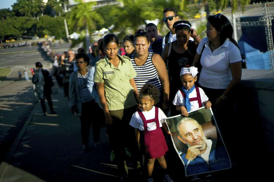 A child holds a poster of Fidel Castro as mourners wait their turn to visit the memorial site for the late leader at the Revolution Plaza in Havana, Cuba, Tuesday. Photo: Ramon Espinosa — The Associated Press   / Copyright 2016 The Associated Press. All rights reserved.