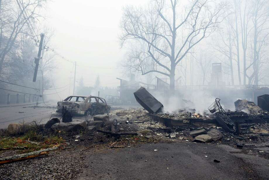 A structure and vehicle are damaged from the wildfires around Gatlinburg, Tenn., on  Tuesday, Nov. 29, 2016. Rain had begun to fall in some areas, but experts predicted it would not be enough to end the relentless drought that has spread across several Southern states and provided fuel for fires now burning for weeks in states including Tennessee, Georgia and North Carolina. Photo: Michael Patrick — Knoxville News Sentinel Via AP / ©2016