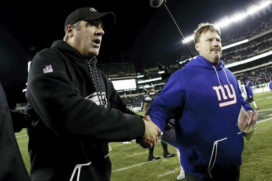 Eagles coach Doug Pederson, left, and Giants coach Ben McAdoo meet after Thursday's game. Photo: Michael Perez — The Associated Press   / FR168006 AP