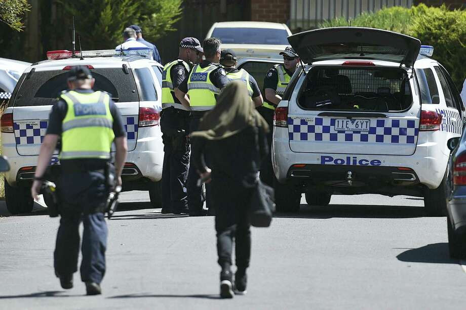 Police accompany a woman as they attend the scene where a house was raided at Meadow Heights in Melbourne, Australia, Friday, Dec. 23, 2016. Police in Australia detained five suspects who were allegedly planning a series of Christmas Day bomb attacks in the heart of the country's second largest city, officials said Friday. Photo: Julian Smith — AAP Image Via AP    / AAP Image