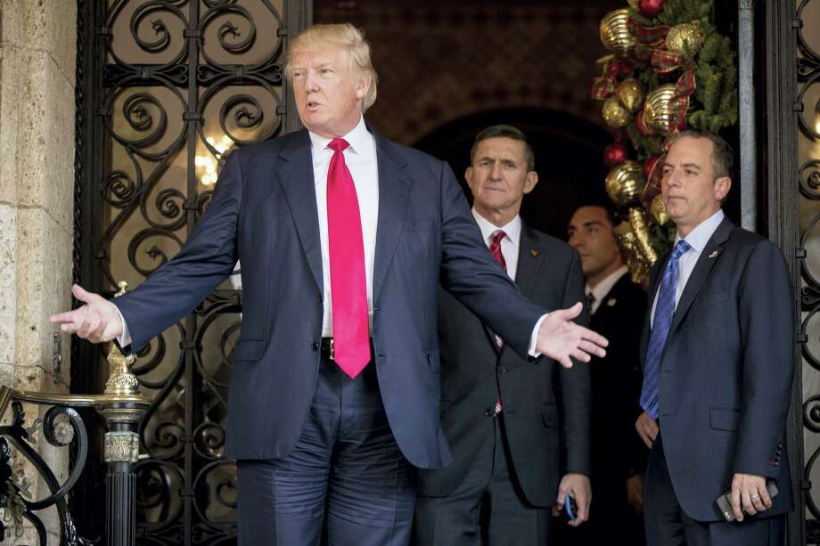 President-elect Donald Trump, left, accompanied by Trump Chief of Staff Reince Priebus, right, and Retired Gen. Michael Flynn, a senior adviser to Trump, center, speaks to members of the media at Mar-a-Lago, in Palm Beach, Fla., Wednesday, Dec. 21, 2016. Photo: Andrew Harnik — AP Photo   / Copyright 2016 The Associated Press. All rights reserved.