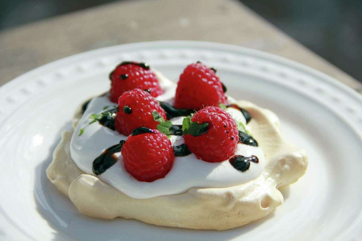 A pavlova is a meringue shell baked at low heat until the outside is barely golden crisp, but the inside remains soft and billowy.