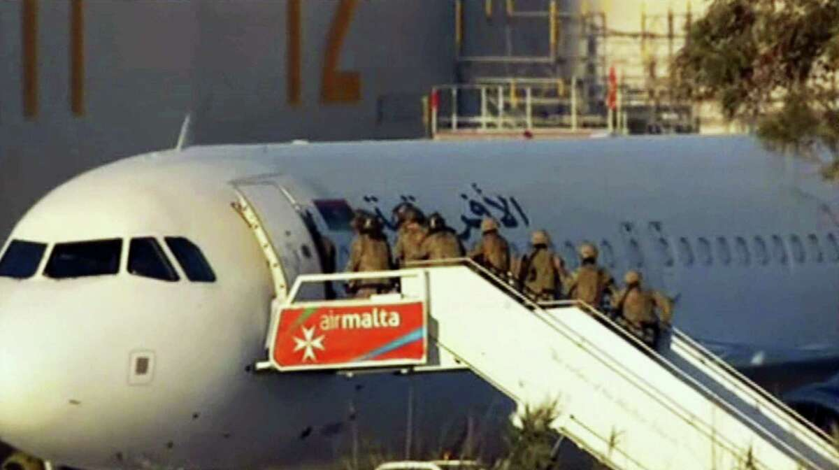 An Afriqiyah Airways plane sits on the tarmac at Malta's Luqa International airport as military personnel approach it, Friday, Dec. 23, 2016. After hours of tense negotiations, Libyans who hijacked the plane from Libya to Malta and threatened to blow it up surrendered peacefully Friday, allowing the passengers and crew to leave the plane before walking out themselves with the last of the crew.