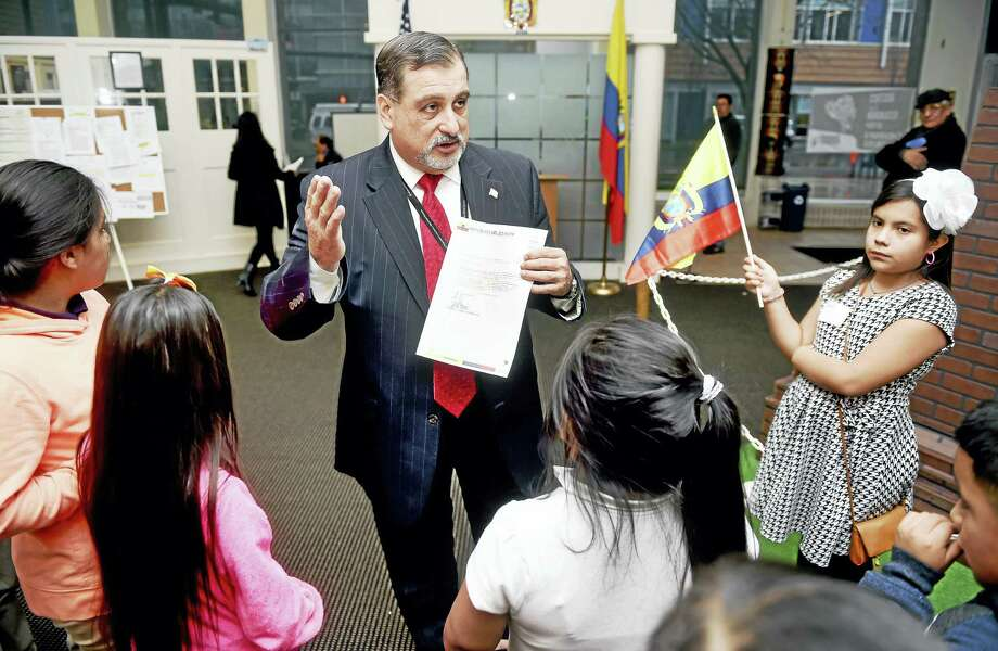 Consul General Raul Erazo Velarde, center, gives a tour of the Consulate of Ecuador in New Haven to nine-year-old Sofia Almeida, right, carrying the flag of Ecuador, and her classmates from Truman School in New Haven. Photo: Arnold Gold — New Haven Register