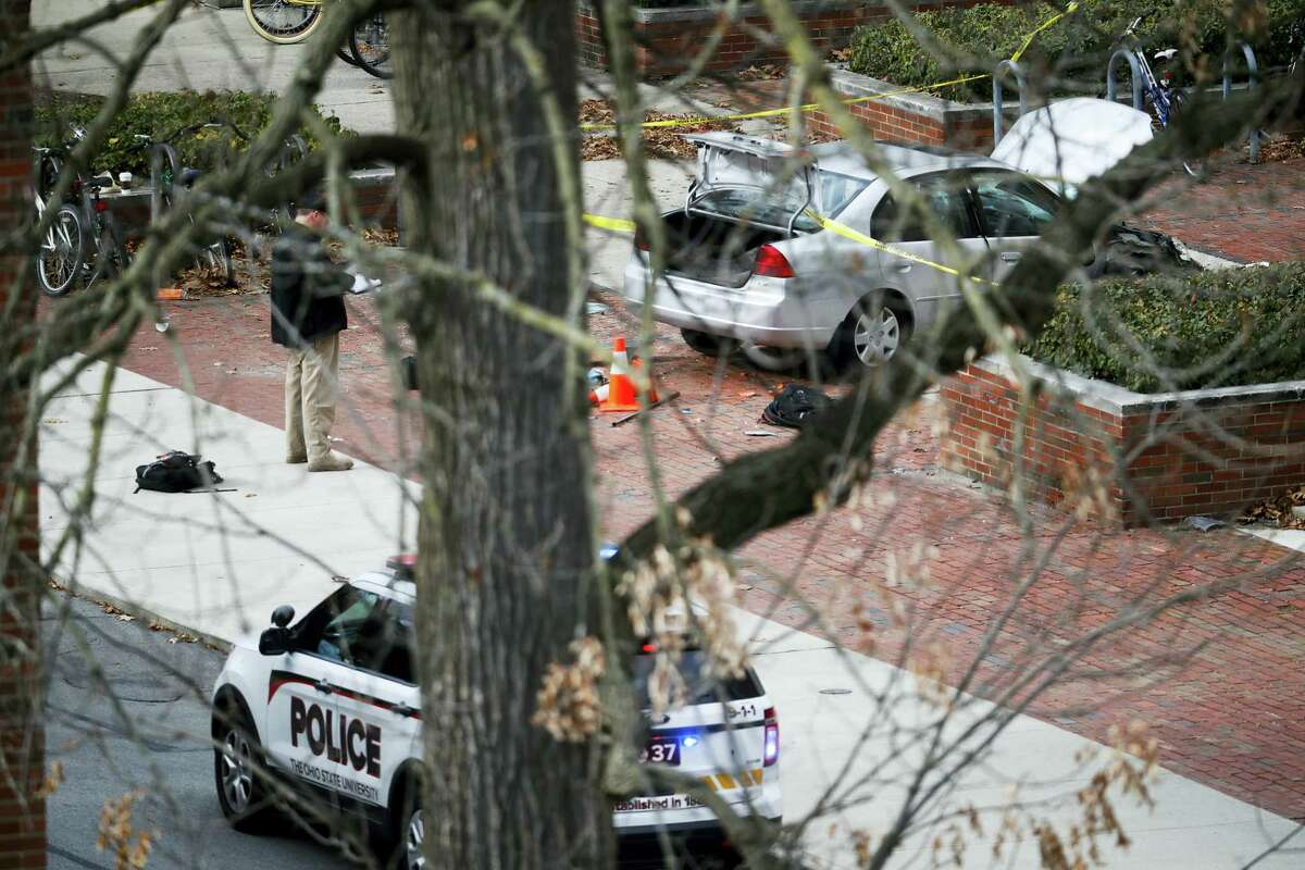 A car inside a police line sits on the sidewalk as authorities respond to an attack on campus at Ohio State University, Monday, Nov. 28, 2016, in Columbus, Ohio. Several were injured after a man plowed his car into a group of pedestrians at the university and began stabbing people with a butcher knife Monday before he was shot to death by a police officer.