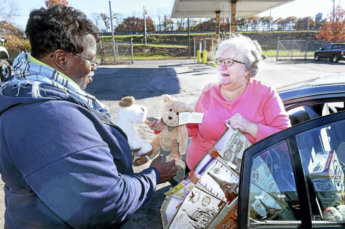Honda Smith, left, accepts stuffed animals and other toys from Jo-Ann Giammattei of New Haven for the Fill-a-Dumpster Toy Drive at the New Haven Public Works Department in New Haven recently.
