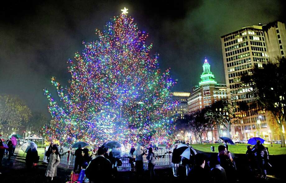 People pass by the Christmas tree after it was lit on the New Haven Green in 2015. Photo: Arnold Gold — New Haven Register