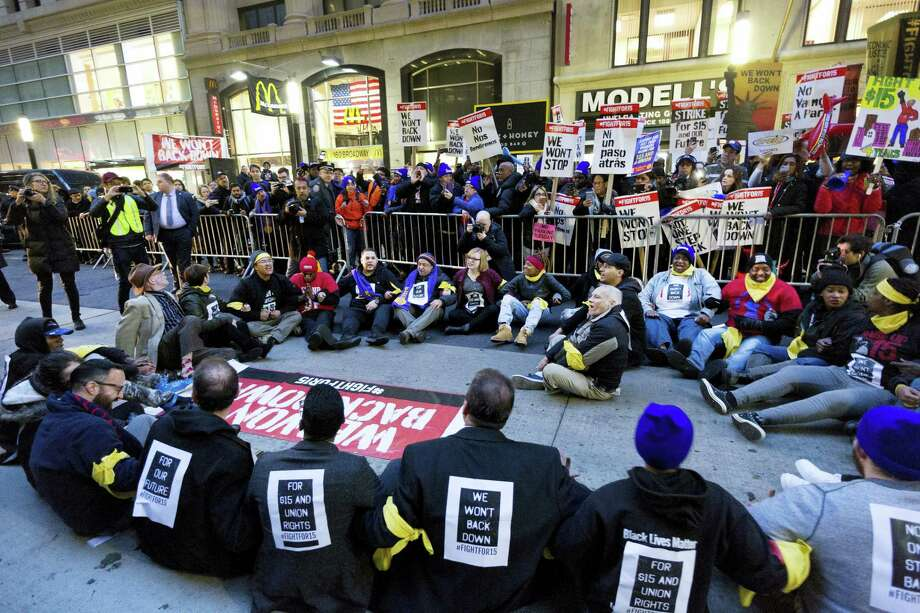 A crowd of about 350 protesters stand on Broadway in front of a McDonald's restaurant, Tuesday, Nov. 29, 2016, in New York. About 25 of the chanting minimum-wage protesters, foreground, were arrested. The event was part of the National Day of Action to Fight for $15. The campaign seeks higher hourly wages, including for workers at fast-food restaurants and airports. Photo: Mark Lennihan — AP Photo / Copyright 2016 The Associated Press. All rights reserved.
